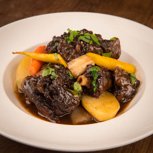 Braised beef oxtail in red wine sauce with baby carrots Queue de boeuf